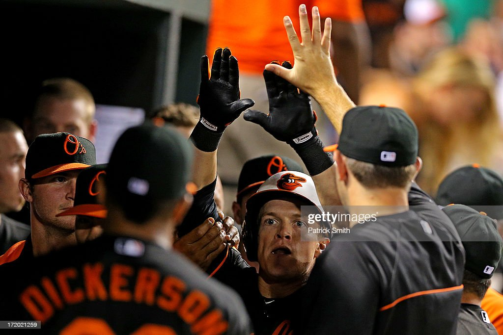 <a gi-track='captionPersonalityLinkClicked' href=/galleries/search?phrase=Nate+McLouth&family=editorial&specificpeople=536572 ng-click='$event.stopPropagation()'>Nate McLouth</a> #9 of the Baltimore Orioles is greeted in the dugout after hitting a solo home run against the New York Yankees in the third inning at Oriole Park at Camden Yards on June 30, 2013 in Baltimore, Maryland. The Baltimore Orioles won, 4-2.