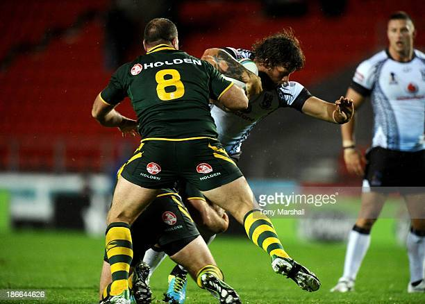 Nate Myles and Matthew Scott of Australia tackles Ashton Sims of Fiji during the Rugby League World Cup Group A match between Australia and Fiji at...
