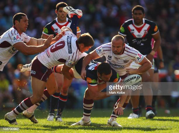Nate Myles of the Roosters gets a pass away as he is tackled during the round 25 NRL match between the Sydney Roosters and the Manly Sea Eagles at...