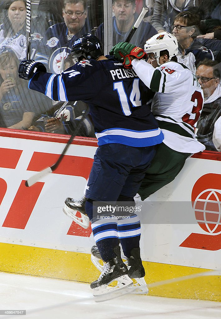 <a gi-track='captionPersonalityLinkClicked' href=/galleries/search?phrase=Nate+Prosser&family=editorial&specificpeople=6851127 ng-click='$event.stopPropagation()'>Nate Prosser</a> #39 of the Minnesota Wild is checked hard into the boards by Anthony Peluso #14 of the Winnipeg Jets during second period action at the MTS Centre on December 27, 2013 in Winnipeg, Manitoba, Canada.