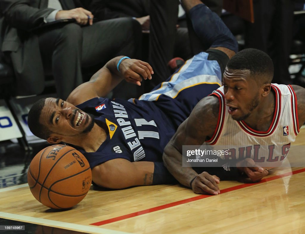 <a gi-track='captionPersonalityLinkClicked' href=/galleries/search?phrase=Nate+Robinson&family=editorial&specificpeople=208906 ng-click='$event.stopPropagation()'>Nate Robinson</a> #2 of the Chicago Bulls and Mike Conley #11 of the Memphis Grizzles watch the ball roll out of bounds after diving at the United Center on January 19, 2013 in Chicago, Illinois. The Grizzlies defeated the Bulls 85-82 in overtime.