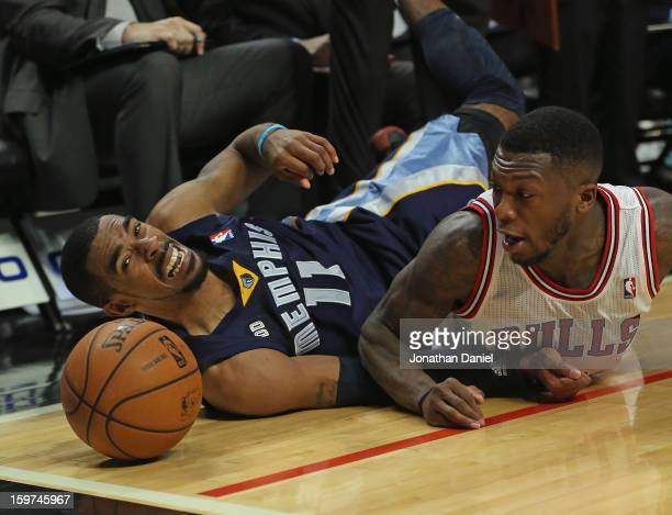 Nate Robinson of the Chicago Bulls and Mike Conley of the Memphis Grizzles watch the ball roll out of bounds after diving at the United Center on...