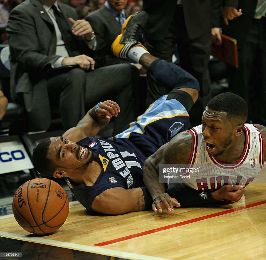 Nate Robinson #2 of the Chicago Bulls and Mike Conley #11 of the Memphis Grizzles watch the ball roll out of bounds after diving at the United Center on January 19, 2013 in Chicago, Illinois. The Grizzlies defeated the Bulls 85-82 in overtime.