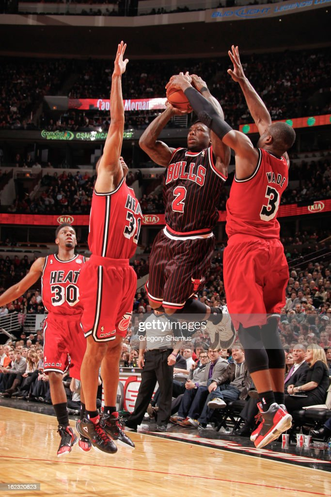 Nate Robinson #2 of the Chicago Bulls attempts a three-pointer against Shane Battier #31 and Dwyane Wade #3 of the Miami Heat on February 21, 2013 at the United Center in Chicago, Illinois.