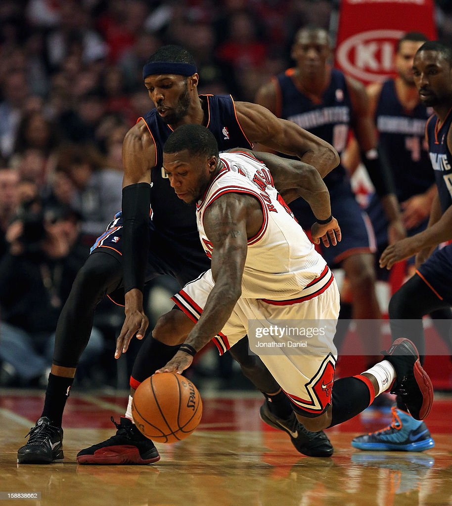Nate Robinson #2 of the Chicago Bulls chases a loose ball under pressure from Hakim Warrick #21 of the Charlotte Bobcats at the United Center on December 31, 2012 in Chicago, Illinois.