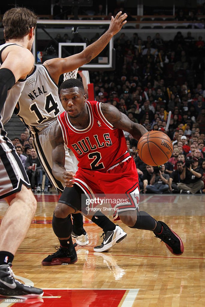 Nate Robinson #2 of the Chicago Bulls drives ahead of Gary Neal #14 of the San Antonio Spurs on February 11, 2013 at the United Center in Chicago, Illinois.