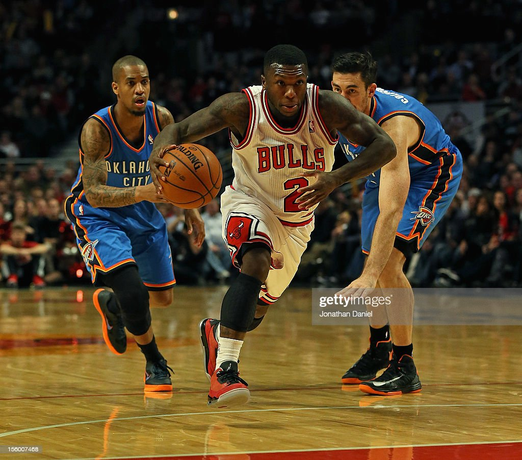 <a gi-track='captionPersonalityLinkClicked' href=/galleries/search?phrase=Nate+Robinson&family=editorial&specificpeople=208906 ng-click='$event.stopPropagation()'>Nate Robinson</a> #2 of the Chicago Bulls drives between <a gi-track='captionPersonalityLinkClicked' href=/galleries/search?phrase=Eric+Maynor&family=editorial&specificpeople=4194194 ng-click='$event.stopPropagation()'>Eric Maynor</a> #6 (L) and <a gi-track='captionPersonalityLinkClicked' href=/galleries/search?phrase=Nick+Collison&family=editorial&specificpeople=202843 ng-click='$event.stopPropagation()'>Nick Collison</a> #4 of the Oklahoma City Thunder at the United Center on November 8, 2012 in Chicago, Illinois. The Thunder defeated the Bulls 97-91.