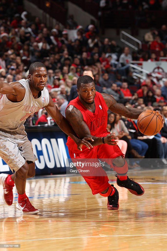 Nate Robinson #2 of the Chicago Bulls drives past Toney Douglas #15 of the Houston Rockets during a Christmas Day game on December 25, 2012 at the United Center in Chicago, Illinois.