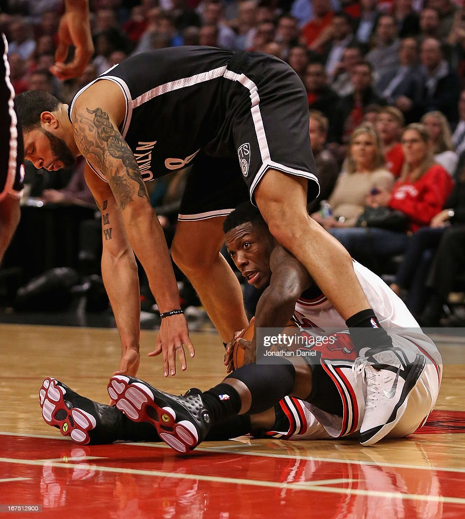 <a gi-track='captionPersonalityLinkClicked' href=/galleries/search?phrase=Nate+Robinson&family=editorial&specificpeople=208906 ng-click='$event.stopPropagation()'>Nate Robinson</a> #2 of the Chicago Bulls ends up under <a gi-track='captionPersonalityLinkClicked' href=/galleries/search?phrase=Deron+Williams&family=editorial&specificpeople=203215 ng-click='$event.stopPropagation()'>Deron Williams</a> #8 of the Brooklyn Nets after chasing down a loose ball in Game Three of the Eastern Conference Quarterfinals during the 2013 NBA Playoffs at the United Center on April 25, 2013 in Chicago, Illinois. The Bulls defeated the Nets 79-76.
