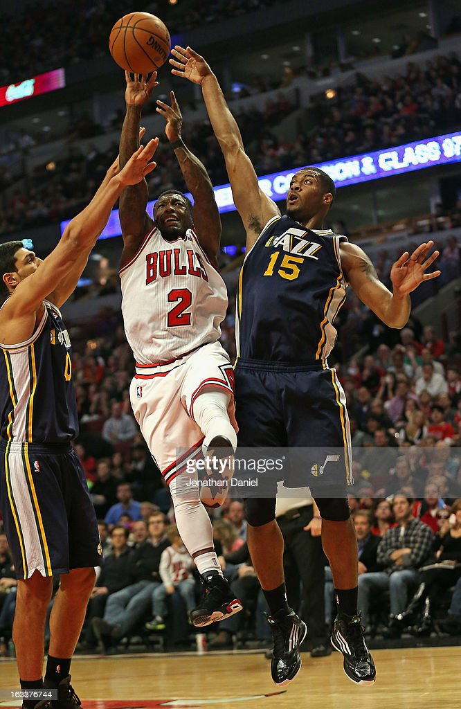 <a gi-track='captionPersonalityLinkClicked' href=/galleries/search?phrase=Nate+Robinson&family=editorial&specificpeople=208906 ng-click='$event.stopPropagation()'>Nate Robinson</a> #2 of the Chicago Bulls goes up for a shot between <a gi-track='captionPersonalityLinkClicked' href=/galleries/search?phrase=Enes+Kanter&family=editorial&specificpeople=5621416 ng-click='$event.stopPropagation()'>Enes Kanter</a> #0 and <a gi-track='captionPersonalityLinkClicked' href=/galleries/search?phrase=Derrick+Favors&family=editorial&specificpeople=5792014 ng-click='$event.stopPropagation()'>Derrick Favors</a> #15 of the Utah Jazz at the United Center on March 8, 2013 in Chicago, Illinois.