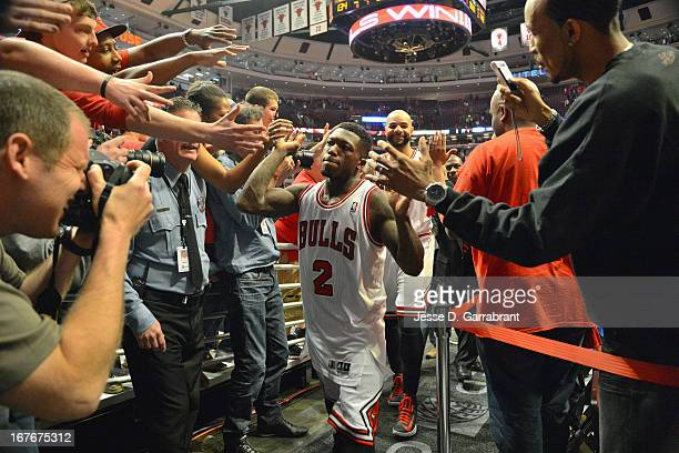 Nate Robinson of the Chicago Bulls highfives fans after the win in triple over time against the Brooklyn Nets in Game Four of the Eastern Conference...