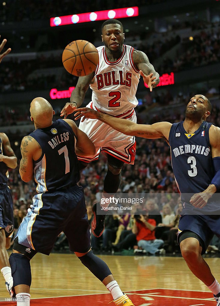 Nate Robinson #2 of the Chicago Bulls leaps to pass between Jerryd Bayless #7 and Wayne Ellington #3 of the Memphis Grizzles at the United Center on January 19, 2013 in Chicago, Illinois. The Grizzlies defeated the Bulls 85-82 in overtime.