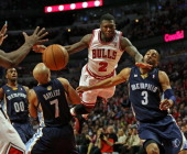 Nate Robinson of the Chicago Bulls leaps to pass between Jerryd Bayless and Wayne Ellington of the Memphis Grizzles at the United Center on January...
