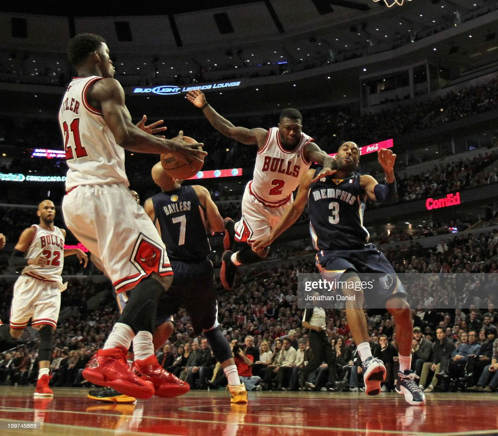 Nate Robinson #2 of the Chicago Bulls leaps to pass to Jimmy Butler #21 between Jerryd Bayless #7 and Wayne Ellington #3 of the Memphis Grizzles at the United Center on January 19, 2013 in Chicago, Illinois. The Grizzlies defeated the Bulls 85-82 in overtime.