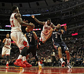 Nate Robinson of the Chicago Bulls leaps to pass to Jimmy Butler between Jerryd Bayless and Wayne Ellington of the Memphis Grizzles at the United...