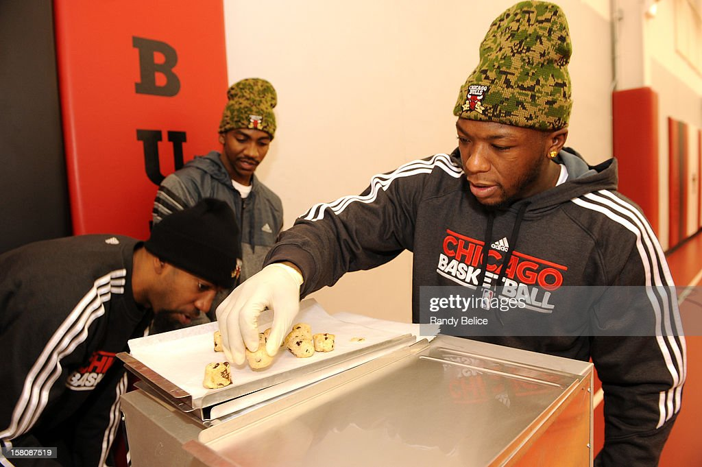 Nate Robinson of the Chicago Bulls prepares a tray of cookies for baking while team mates Richard Hamilton (L) and Marquis Teague man the oven during the team's USO / Chicago Housing Authority Holiday Party on December 9, 2012 at the Sheri L. Berto Center in Deerfield, Illinois.