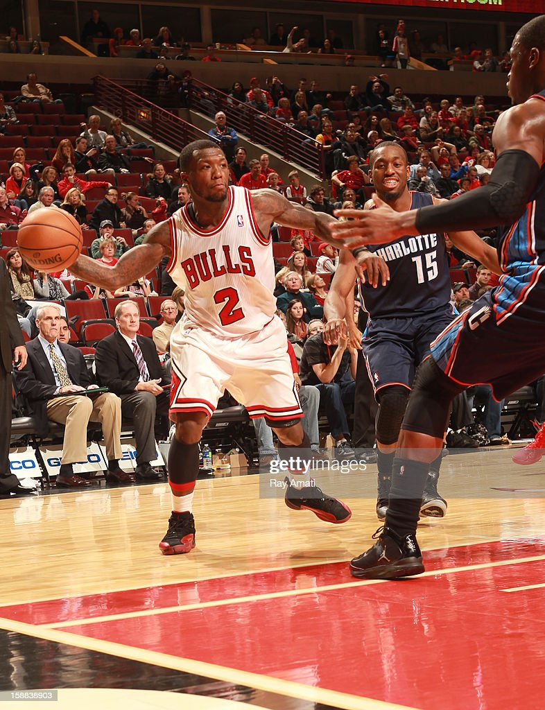 Nate Robinson #2 of the Chicago Bulls prepares to throw a pass beyond Jeff Adrien #4 and Kemba Walker #15 of the Charlotte Bobcats on December 31, 2012 at the United Center in Chicago, Illinois.