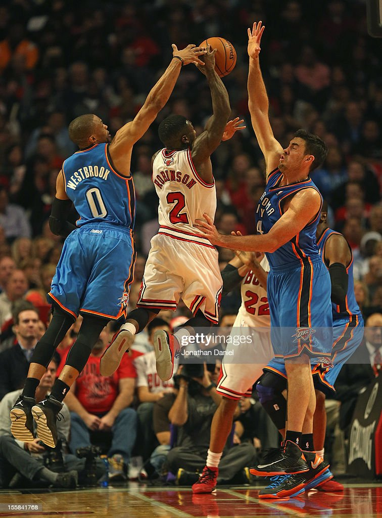 Nate Robinson #2 of the Chicago Bulls puts up a shot between Russell Westbrook #0 and Nick Collison #4 of the Oklahoma City Thunder at the United Center on November 8, 2012 in Chicago, Illinois.