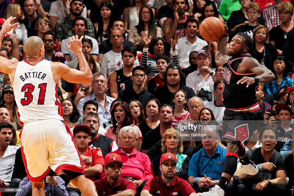 Nate Robinson #2 of the Chicago Bulls saves a ball from going out-of-bounds by throwing it off Shane Battier #31 of the Miami Heat on January 4, 2013 at American Airlines Arena in Miami, Florida.