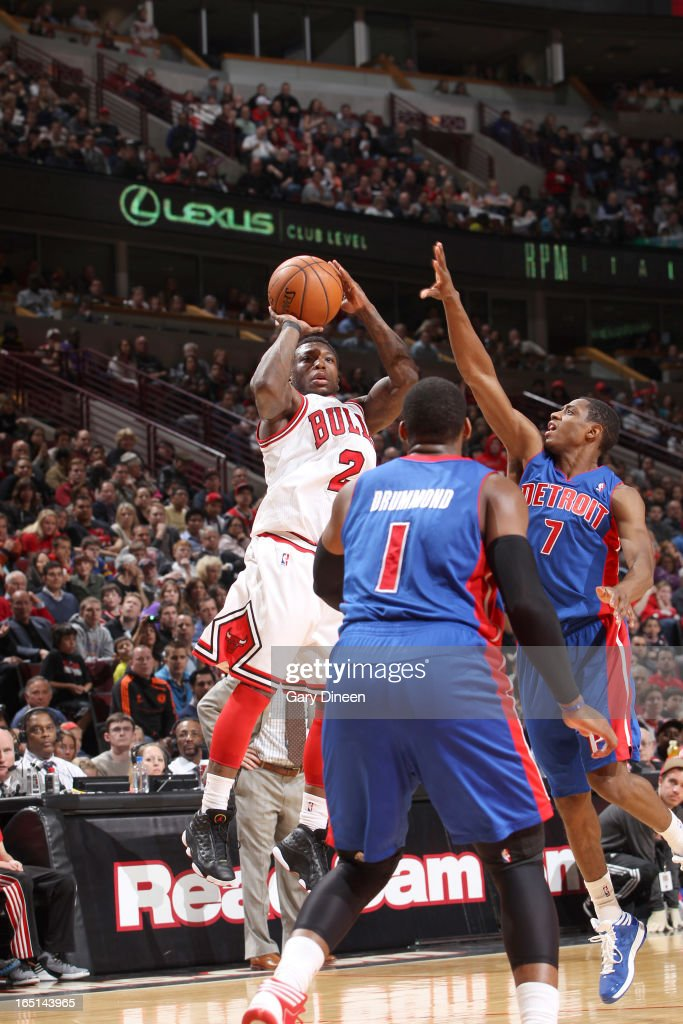 Nate Robinson #2 of the Chicago Bulls shoots over Andre Drummond #1 and Brandon Knight #7 of the Detroit Pistons on March 31, 2013 at the United Center in Chicago, Illinois.