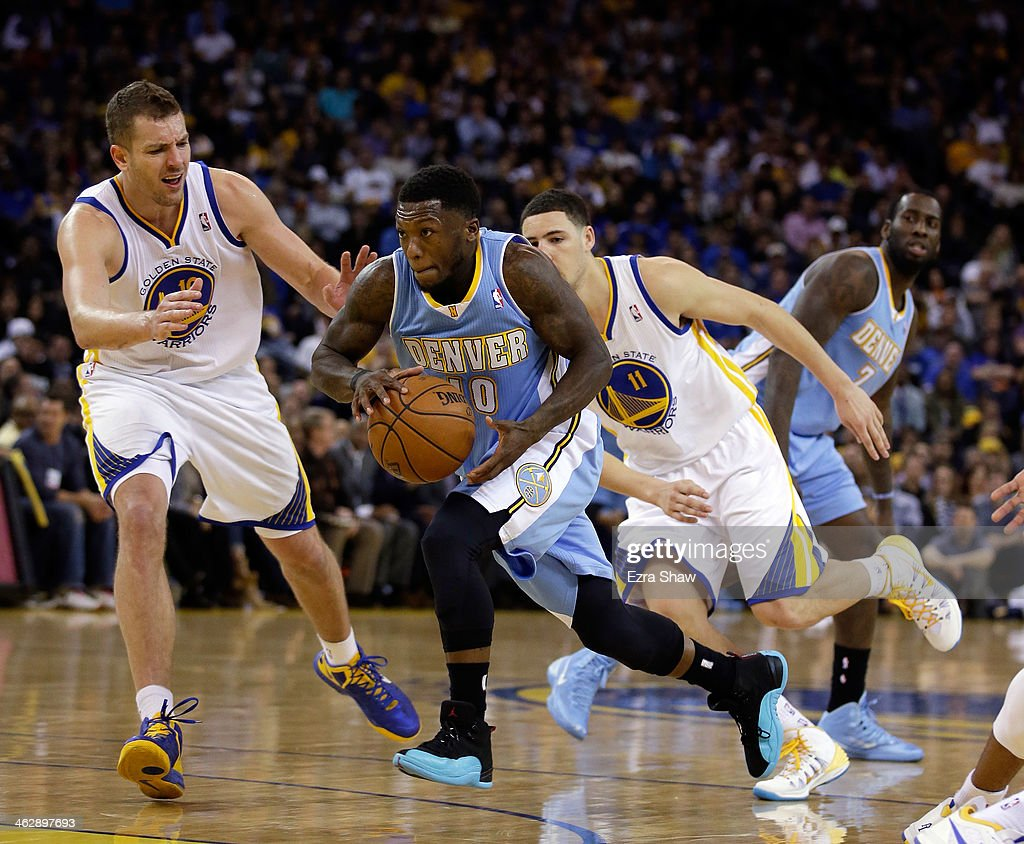Nate Robinson #10 of the Denver Nuggets dribbles past David Lee #10 and Klay Thompson #11 of the Golden State Warriors at ORACLE Arena on January 15, 2014 in Oakland, California.