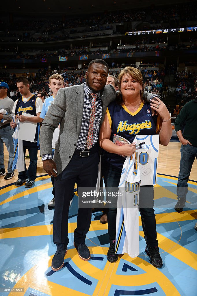 Nate Robinson #10 of the Denver Nuggets gives a jersey to a fan before a game against the Golden State Warriors on April 16, 2014 at the Pepsi Center in Denver, Colorado.