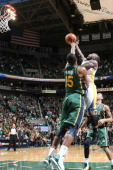 Nate Robinson of the Golden State Warriors looks for the winning layup and is blocked by Derrick Favors of the Utah Jazz at Energy Solutions Arena on...