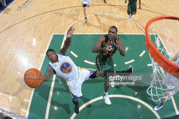 Nate Robinson of the Golden State Warriors pulls down a rebound over Paul Millsap of the Utah Jazz at Energy Solutions Arena on March 17 2012 in Salt...