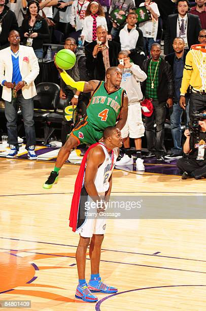 Nate Robinson of the New York Knicks attempts a dunk by jumping over Dwight Howard of the Orlando Magic during the Sprite Slam Dunk Contest as part...