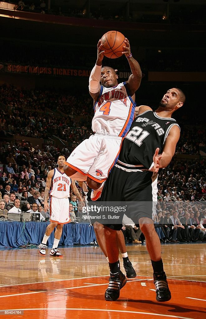 Nate Robinson #4 of the New York Knicks puts up a shot against <a gi-track='captionPersonalityLinkClicked' href=/galleries/search?phrase=Tim+Duncan&family=editorial&specificpeople=201467 ng-click='$event.stopPropagation()'>Tim Duncan</a> #21 of the San Antonio Spurs during the game on February 17, 2009 at Madison Square Garden in New York City. The Knicks won 112-107.