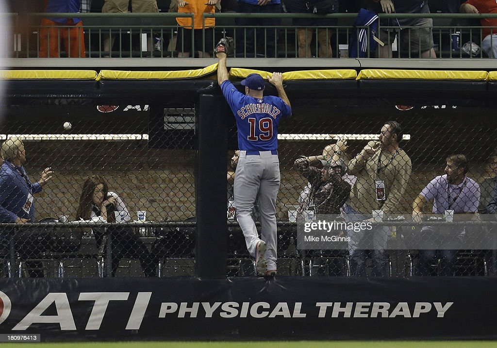 <a gi-track='captionPersonalityLinkClicked' href=/galleries/search?phrase=Nate+Schierholtz&family=editorial&specificpeople=803208 ng-click='$event.stopPropagation()'>Nate Schierholtz</a> #19 of the Chicago Cubs climbs the wall in right field as Sean Halton's of the Milwaukee Brewers ball goes over the wall for a grand slam in the bottom of the first inning at Miller Park on September 18, 2013 in Milwaukee, Wisconsin.