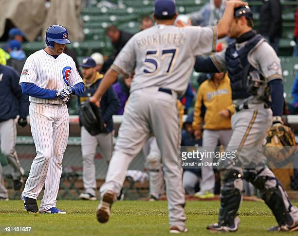 Nate Schierholtz of the Chicago Cubs walks back to the dugout after making the final out of the game as Francisco Rodriquez and Jonathan Lucroy of...