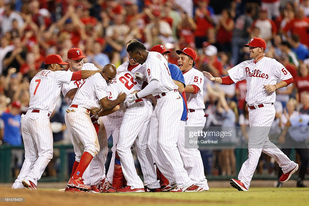 <a gi-track='captionPersonalityLinkClicked' href=/galleries/search?phrase=Nate+Schierholtz&family=editorial&specificpeople=803208 ng-click='$event.stopPropagation()'>Nate Schierholtz</a> #22 of the Philadelphia Phillies is congratulated by teammates after hitting an RBI single to win the game against the Colorado Rockies at Citizens Bank Park on September 7, 2012 in Philadelphia, Pennsylvania. The Phillies won 3-2.