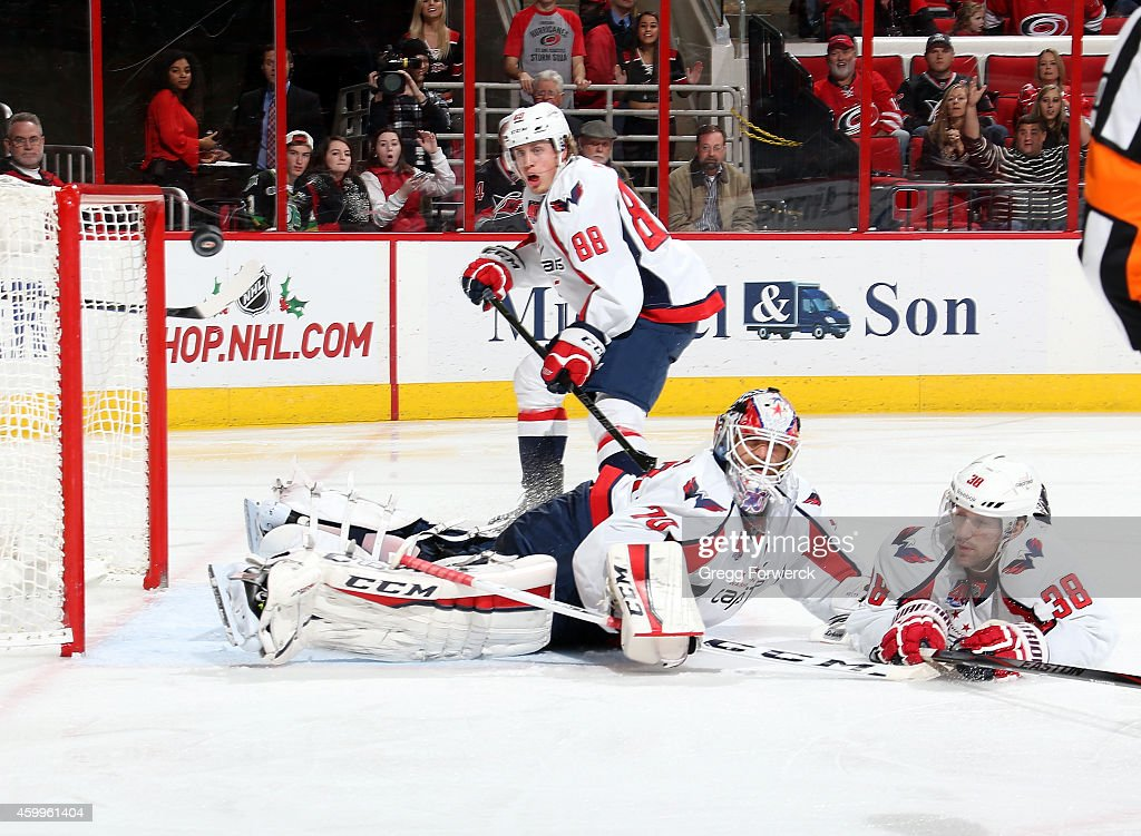 Nate Schmidt #88, Braden Holtby #70 and Jack Hillen #38 of the Washington Capitals react as a Carolina Hurricanes shot just misses the goal during an NHL game at PNC Arena on December 4, 2014 in Raleigh, North Carolina.