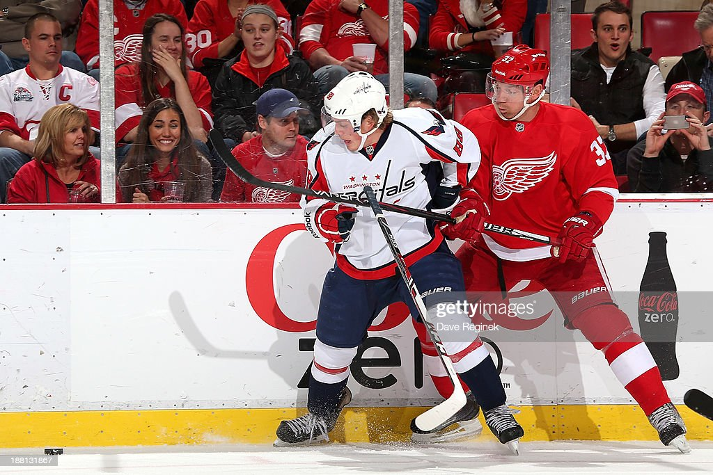 Nate Schmidt #88 of the Washington Capitals and Mikael Samuelsson #37 of the Detroit Red Wings battle for the puck along the boards during an NHL game at Joe Louis Arena on November 15, 2013 in Detroit, Michigan.