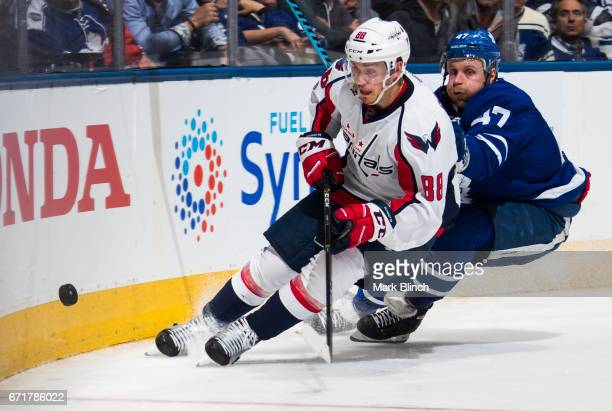 Nate Schmidt of the Washington Capitals skates against Leo Komarov of the Toronto Maple Leafs during the third period in Game Four of the Eastern...