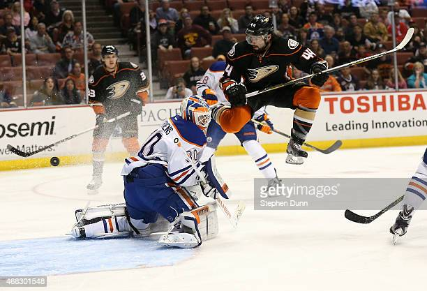 Nate Thompson of the Anaheim Ducks jumps in the air as a shot by Duck Francois Beauchemin gets by goalie Ben Scrivens of the Edmonton Oilers for a...