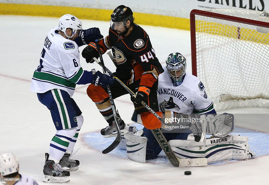 Nate Thompson #44 of the Anaheim Ducks jumps to let the puck through but goalie Ryan Miller #30 of the Vancouver Canucks makes the save as Canuck Yannick Weber #6 defends at Honda Center on December 28, 2014 in Anaheim, California. The Ducks won 2-1 in overtime.