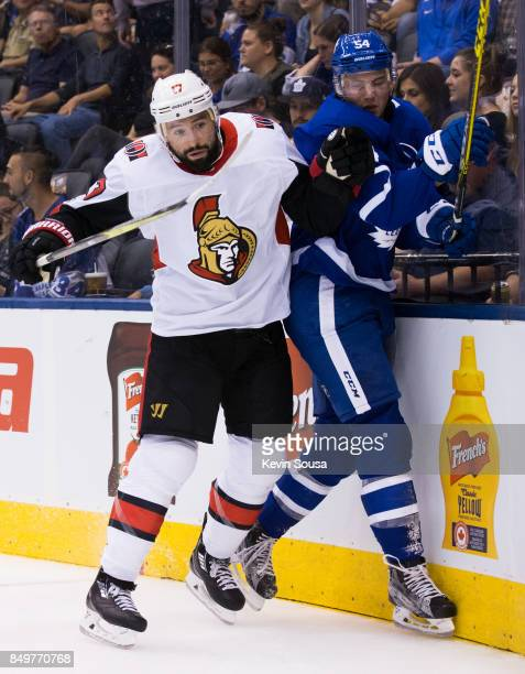 Nate Thompson of the Ottawa Senators checks Justin Holl of the Toronto Maple Leafs during the first period at the Air Canada Centre in their...