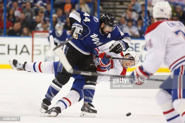Nate Thompson of the Tampa Bay Lightning checks Lars Eller of the Montreal Canadiens during the second period at Tampa Bay Times Forum on December 28...