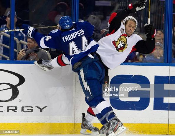 Nate Thompson of the Tampa Bay Lightning checks Matt Gilroy of the Ottawa Senators into the boards at the Tampa Bay Times Forum on March 6 2012 in...