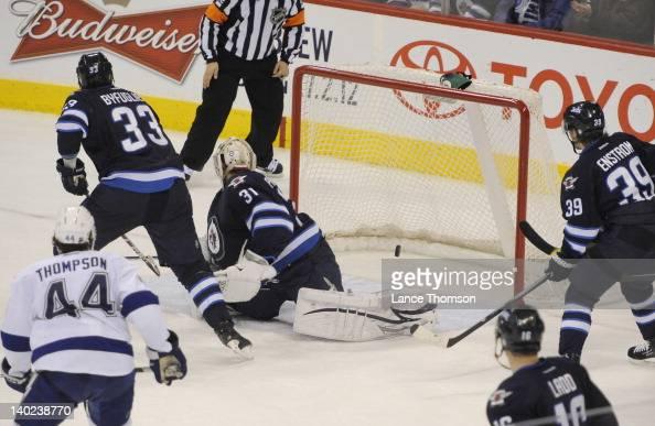 Nate Thompson of the Tampa Bay Lightning Dustin Byfuglien goaltender Ondrej Pavelec Tobias Enstrom and Andrew Ladd of the Winnipeg Jets all watch as...