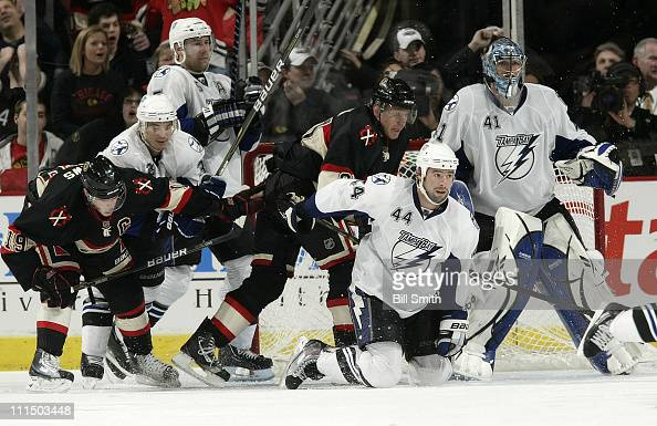 Nate Thompson of the Tampa Bay Lightning falls to his knees in front of teammate goalie Mike Smith and Marian Hossa of the Chicago Blackhawks as...