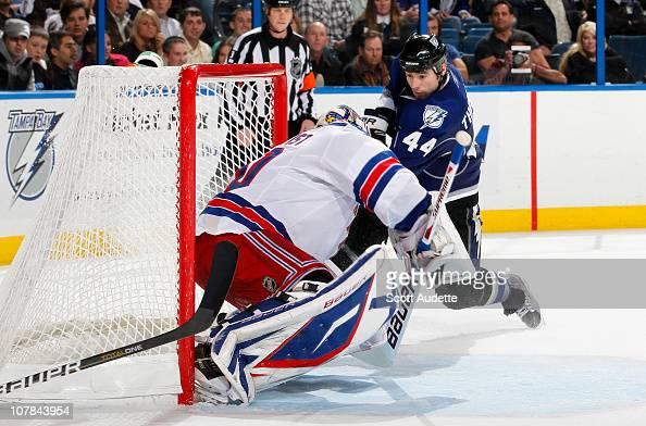 Nate Thompson of the Tampa Bay Lightning shoots the game winning goal in overtime against goaltender Henrik Lundqvist of the New York Rangers at the...