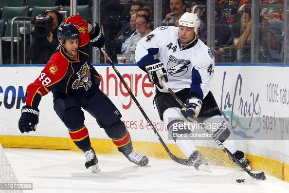 Nate Thompson of the Tampa Bay Lightning skates with the puck against Joe Callahan of the Florida Panthers at the BankAtlantic Center on March 12...
