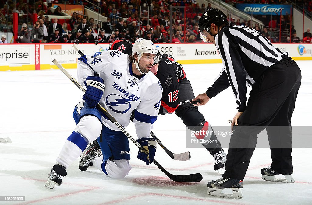 Nate Thompson of the Tampa Bay Lightning takes a face-off against <a gi-track='captionPersonalityLinkClicked' href=/galleries/search?phrase=Eric+Staal&family=editorial&specificpeople=202199 ng-click='$event.stopPropagation()'>Eric Staal</a> #12 of the Carolina Hurricanes during an NHL game on February 23, 2013 at PNC Arena in Raleigh, North Carolina.