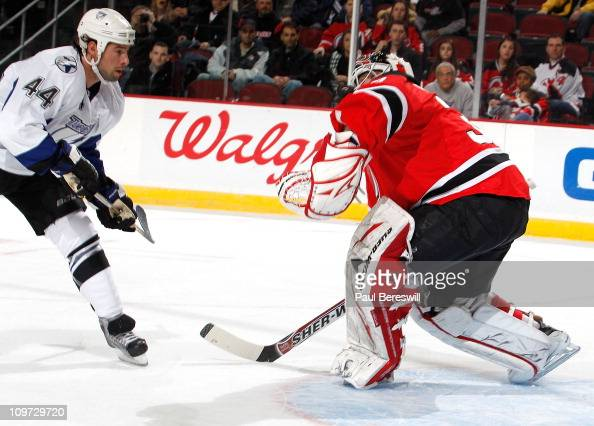 Nate Thompson of the Tampa Bay Lightning watches his shot hit the shoulder of goalie Martin Brodeur of the New Jersey Devils for a save during the...