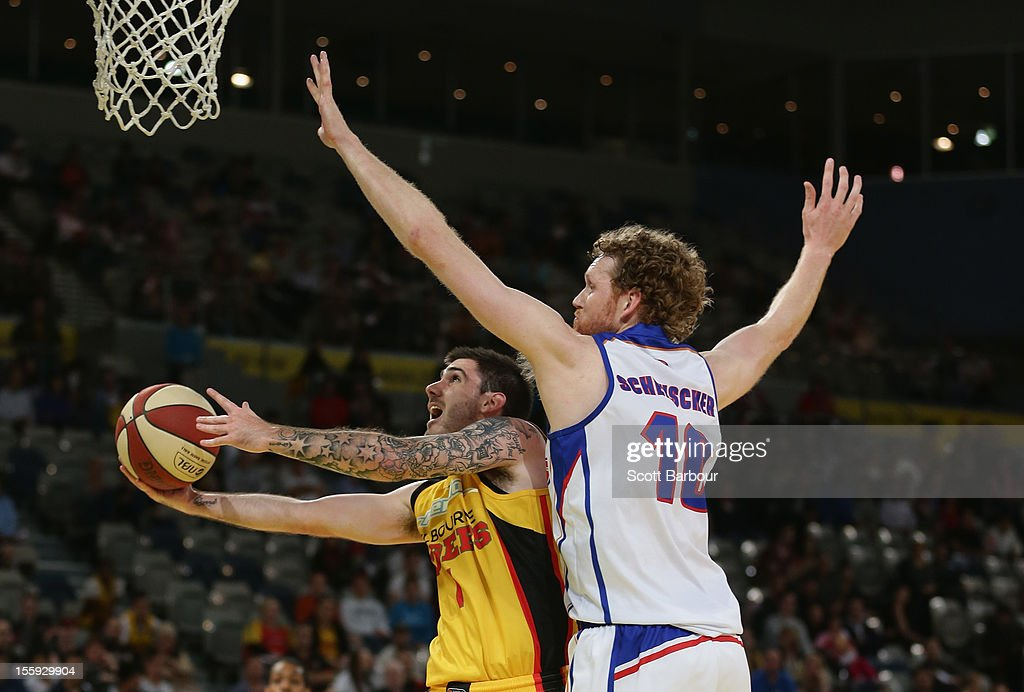 Nate Tomlinson of the Tigers shoots the ball as Luke Schenscher of the 36ers defends during the NBL match between the Melbourne Tigers and the...