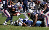 Nate Washington of the Tennessee Titans loses the ball after being hit by Patrick Chung and Jerod Mayo of the New England Patriots during their...