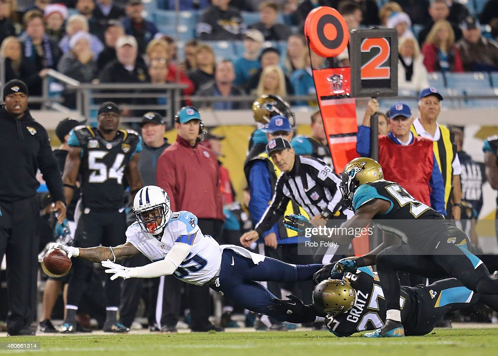 Nate Washington of the Tennessee Titans reaches for extra yards as Dwayne Gratz of the Jacksonville Jaguars defends during the game at EverBank Field...